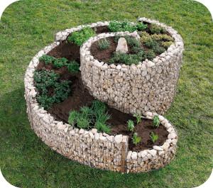 Kräuterspirale mit Erdaushub vom Fertigteich anlegen gefüllt.